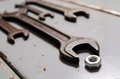 Parecchie chiavi e dado sui precedenti del metallo immagine stock