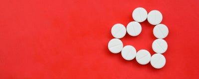 Parecchie compresse bianche si trovano su un fondo rosso luminoso sotto forma di un cuore Immagine di sfondo su medicina e sul to Fotografia Stock Libera da Diritti
