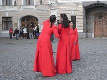 Parecchie donne in vestiti rossi identici che prendono le foto di a vicenda contro lo sfondo delle viste di St Petersburg La Russ Fotografia Stock