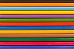 Parecchie matite colorate di legno in una fila per fondo Fotografie Stock