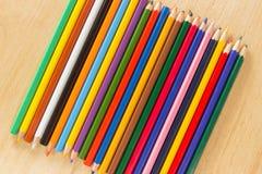 Parecchie matite colorate di legno in una fila per fondo Fotografia Stock