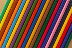 Parecchie matite colorate di legno in una fila per fondo Immagini Stock