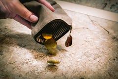 Parecchie monete cadono da una borsa vuota in mano di una donna immagini stock libere da diritti