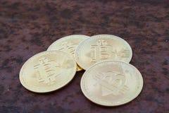 Parecchie monete del bitcoin sulla fine arrugginita del ferro - sull'immagine fotografia stock