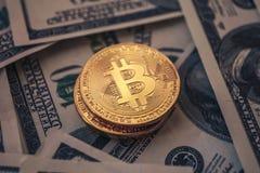 Parecchie monete di Bitcoin sono impilate fra i dollari fotografie stock