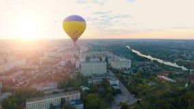 Parecchie mongolfiere che galleggiano sopra la città verso il sol levante sopra l'orizzonte, speranza stock footage