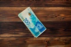 Parecchie nuove banconote degno 200 nuovi shekel israeliani su un fondo di legno Immagini Stock Libere da Diritti