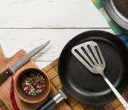 Parecchie padelle vuote della ghisa su un fondo di legno bianco peperoni della miscela in ciotola Fotografia Stock