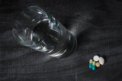 Parecchie pillole e un bicchiere d'acqua su una tavola fotografia stock