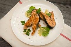 Parecchie spezie rotonde bianche del piatto delle bistecche di color salmone Immagine Stock
