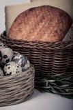 Parecchie varietà di formaggio in un canestro di vimini ed in una quaglia del canestro Fotografie Stock