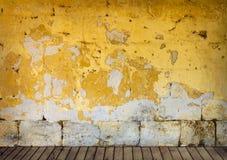 Pared áspera con la peladura de la pintura amarilla Fotos de archivo