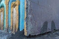 Pared áspera gris del fondo del extracto de la textura del Grunge con yeso de la peladura y arcos azules y amarillos en izquierda Foto de archivo libre de regalías