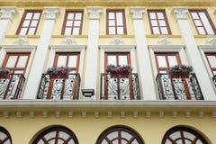 Pared amarilla del edificio en estilo clásico con el balcón Imagen de archivo libre de regalías