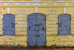 Pared amarilla vieja con los obturadores de la puerta y de la ventana del hierro Fotos de archivo