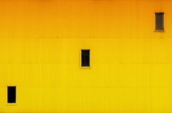 Pared amarillo-naranja brillante con tres ventanas Fotos de archivo libres de regalías
