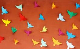 Pared anaranjada con los pájaros de papel coloridos Imágenes de archivo libres de regalías