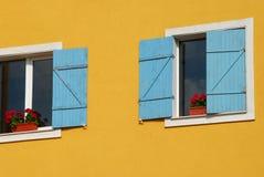 Pared anaranjada de la casa, obturadores azules Foto de archivo libre de regalías