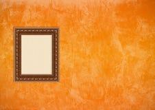 Pared anaranjada del estuco de Grunge con el marco vacío Imagen de archivo