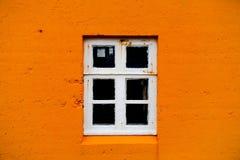 Pared anaranjada y ventana blanca Fotografía de archivo