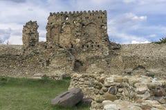 Pared antigua, ruinas de la torre y piedra de molino Foto de archivo