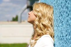 Pared azul y muchacha bonita foto de archivo