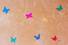 Pared beige pintada con el rodillo de pintura texturizado con las mariposas fotografía de archivo