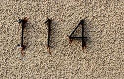 Pared blanca sucia vieja de la roca con los números 114 de forma precipitada pegada imagen de archivo libre de regalías