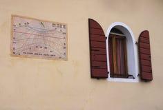 Pared con el reloj de sol viejo y la ventana medieval Fotografía de archivo