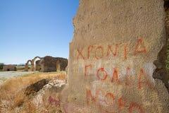 Pared con la pintada y ruinas de la iglesia gótica de las mamáes del santo en el fondo en el pueblo abandonado de Agios Sozomenos Fotos de archivo libres de regalías