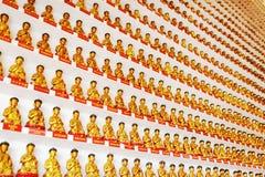 Pared con las pequeñas estatuas de oro de Buda dentro del templo del T Fotos de archivo libres de regalías