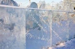 Pared con saludos de la Navidad en ciudad del hielo Imágenes de archivo libres de regalías