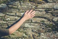 Pared conmovedora de la mano femenina joven fotografía de archivo