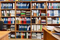 Pared de estantes con las carpetas coloridas del fichero, de un cuarto de la oficina con los papeles y de documentos Imagen de archivo libre de regalías