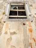 Pared de la casa abandonada, dañada, vieja con una ventana Foto de archivo libre de regalías