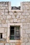 Pared de la casa dañada, vieja con dos ventanas Fotografía de archivo