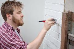 Pared de la casa de la pintura del hombre con el cepillo Mejoras para el hogar de DIY Imagenes de archivo