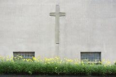 Pared de la iglesia con la cruz del crucifijo y las flores amarillas fotos de archivo libres de regalías