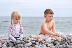 Pared de la piedra de construcción del muchacho y de la muchacha en Rocky Beach Foto de archivo