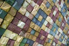 Pared de la piedra salvaje en diversos colores alineados con un modelo imagen de archivo