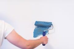 Pared de la pintura de la mano del ` s del decorador fotos de archivo