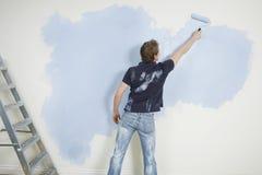Pared de la pintura del hombre con Paintroller Fotos de archivo