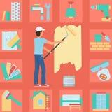 Pared de la pintura del hombre del trabajador con un rodillo Imagen de archivo libre de regalías