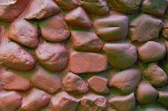Pared de la roca con las piedras redondeadas grandes Pared de piedra pintada con la pintura marrón Fondo de piedra de la fundació Foto de archivo libre de regalías