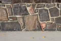 Pared de la roca a lo largo de la acera Foto de archivo libre de regalías