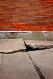 Pared de ladrillo agrietada rota vieja de la acera del cemento fotografía de archivo