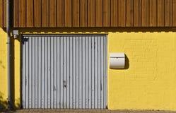 Pared de ladrillo amarilla con la puerta del garaje, el buzón, la bajada de aguas y el revestimiento de madera de madera en la se fotografía de archivo