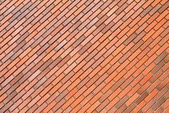 Pared de ladrillo anaranjada, fondo, posición diagonal, textura Foto de archivo