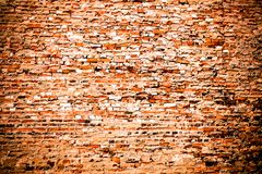 Pared de ladrillo anaranjada roja sucia vieja y resistida cubierta en parte por exceso del cemento y la pintura gris como fondo d fotografía de archivo libre de regalías