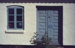 Pared de ladrillo blanca con puertas azules y una ventana foto de archivo